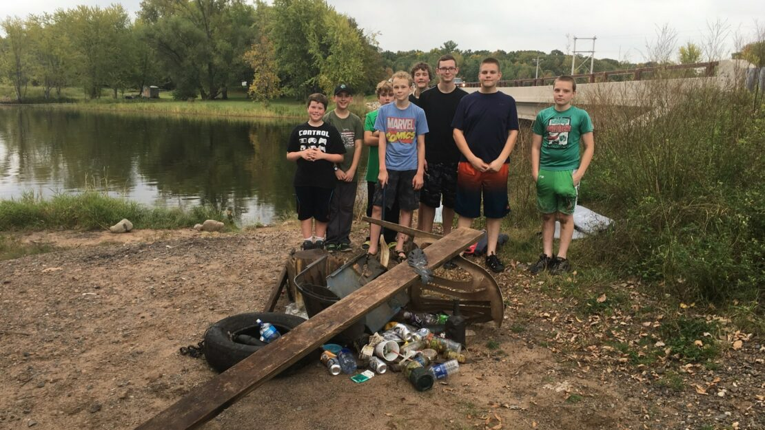 group standing on rivers edge with pile of trash