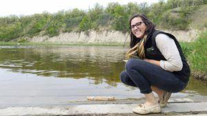 Woman crouching near lake edge