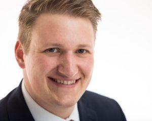 professional headshot of man smiling