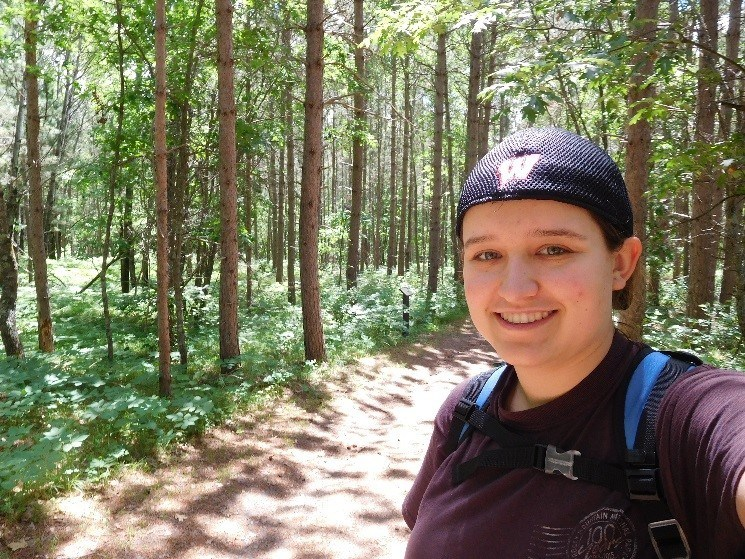 smiling at camera on a hiking trail