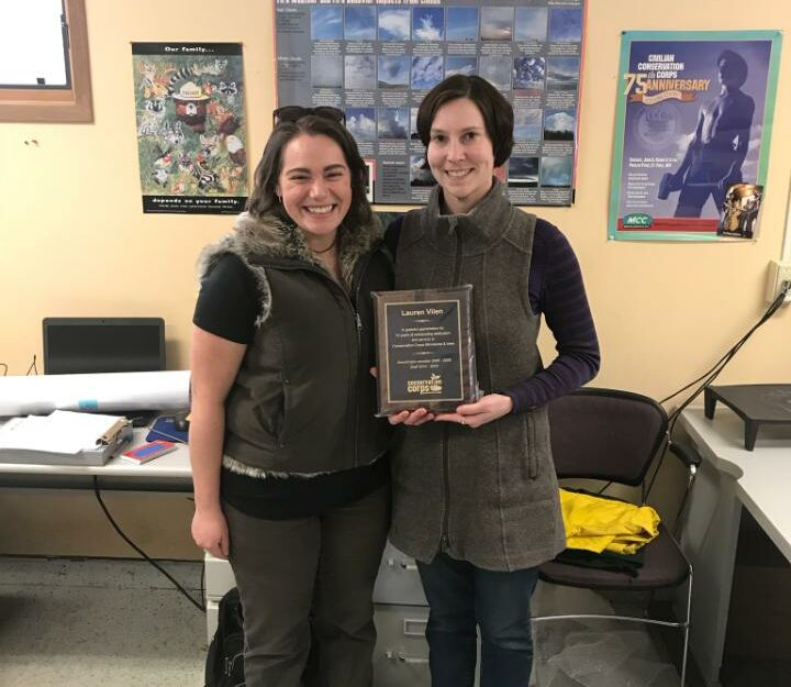 Two people in office with plaque