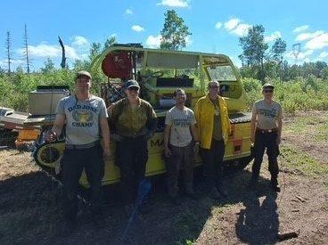 crew in front of heavy vehicle