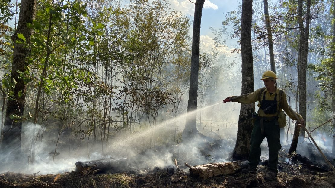backlit firefighter using hose on smoldering fire.