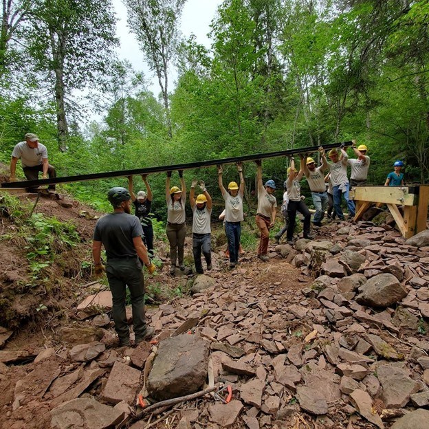 entire crew standing in streambed holding beam above their heads
