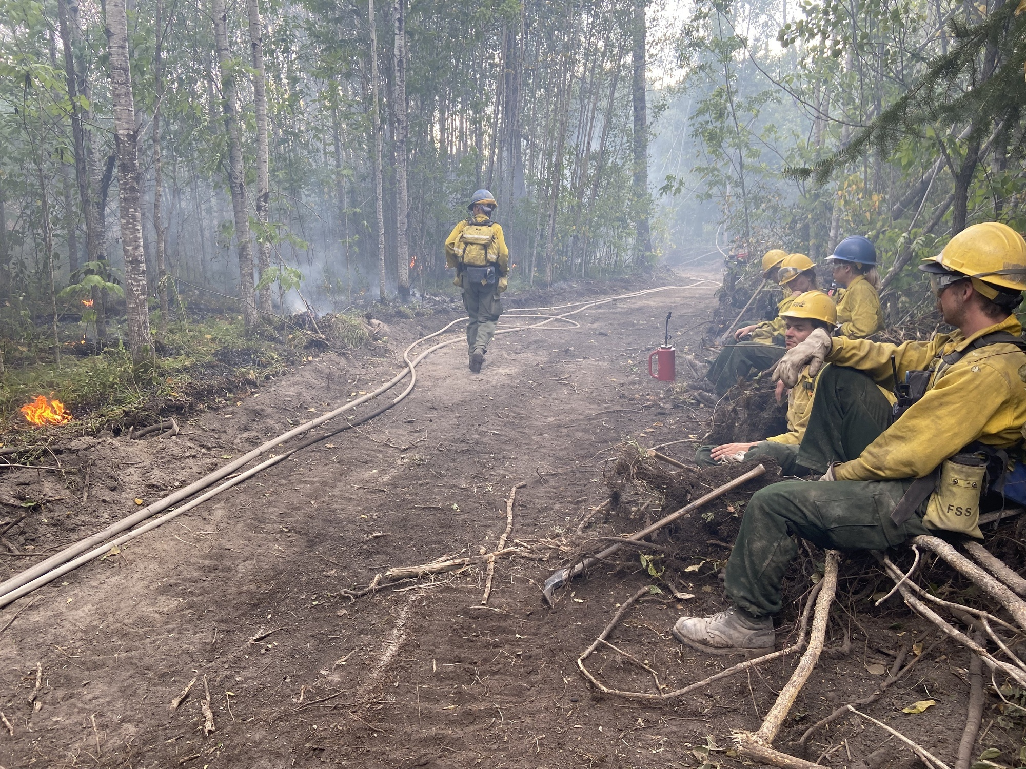 firefighters sitting on a dirt path with fire on the other side